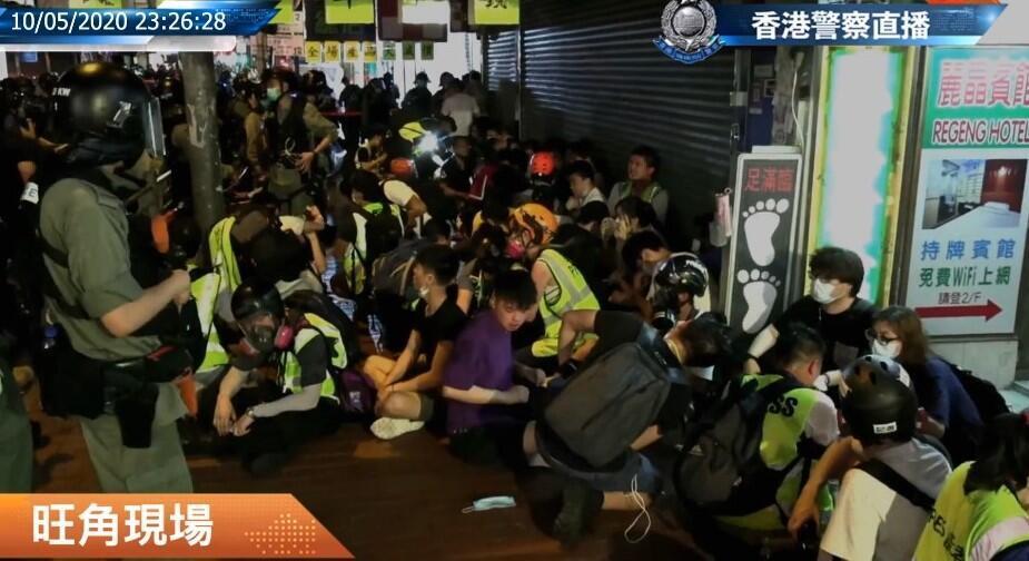 记者被警方围在地上,并限制摄录