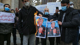 Students of Iran's Basij paramilitary force burn posters depicting US President Donald Trump (top) and President-elect Joe Biden, during a rally in front of the foreign ministry in Tehran