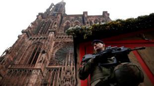 Un soldat monte la garde le 12 décembre devant un chalet du marché de Noël, au pied de la cathédrale de Strasbourg, au lendemain de l'attaque qui a fait trois morts.