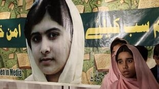 Estudantes paquistanesas diante do retrato de Malala.