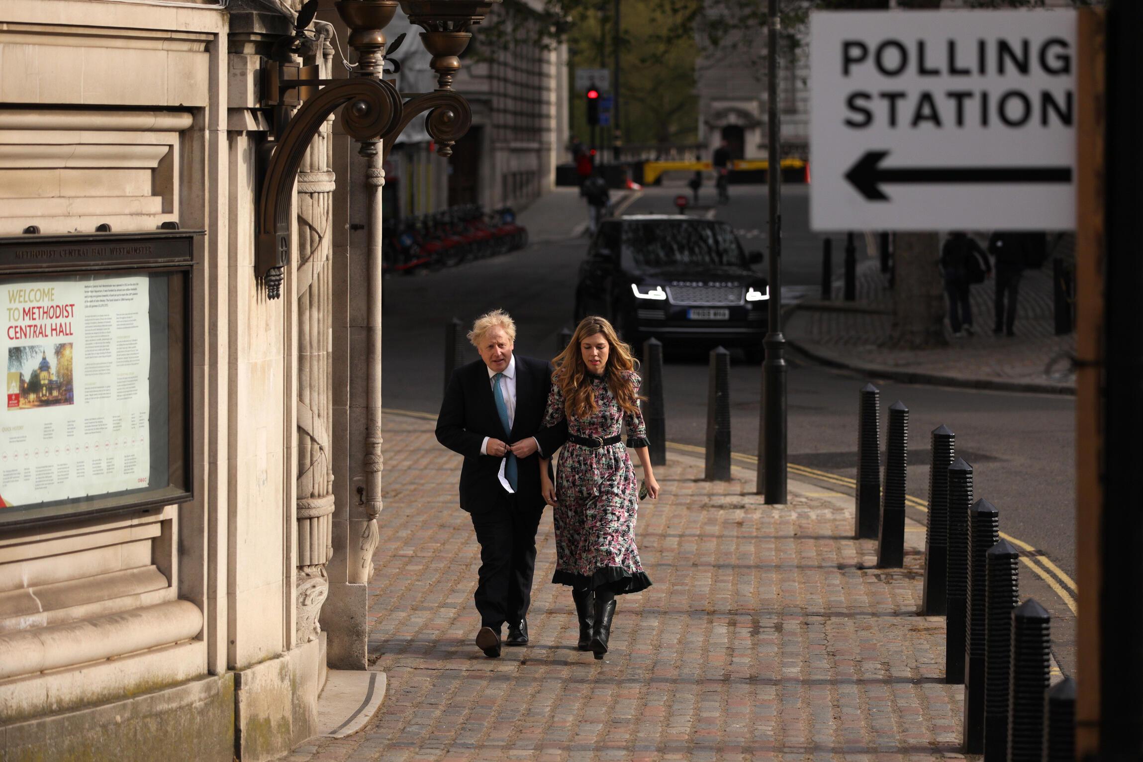 El primer ministro Boris Johnson y su pareja, Carrie Symonds, se dirigen a su centro de votación para las elecciones locales británicas, el 6 de mayo de 2021 en el centro de Londres