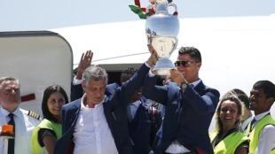 """کریستیانو رونالدو، در کنار مربی تیم، """"فرناندو سانتوس"""" جام پیروزی را در دست داشتند."""