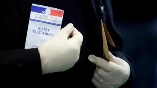 Un homme portant des gants en latex tient sa carte électorale avant de voter dans un bureau de vote lors du premier tour des élections municipales à Paris, alors que la France est aux prises avec une épidémie de coronavirus, le 15 mars 2020.
