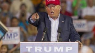 """O candidato Donald Trump causou polêmica com declarações sobre """"bebês-âncora"""", em foto de 21 de agosto de 2015, onde mimetiza o conhecido gesto do """"Mr. America""""."""