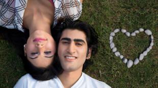 Un couple de jeunes indiens amoureux allongés dans l'herbe.