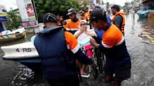 Le personnel de secours aide une dame sur une route inondée à Wellampitiya au Sri Lanka, le 21 mai 2016.