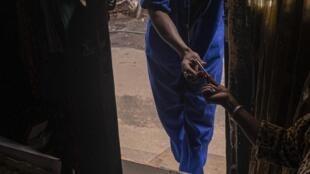 Une femme vend une cigarette à un homme, le 9 avril 2020 alors que le gouvernement a interdit la vente de cigarettes et d'alcool pendant toute la période du confinement en Afrique du Sud.