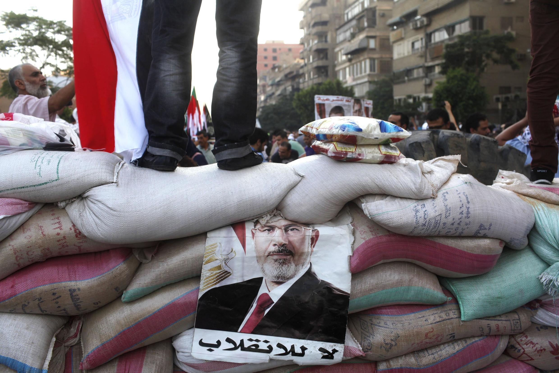 Phe Huynh đệ Hồi giáo trương ảnh tổng thống Ai Cập Mohamed Morsi vừa bị lật đổ trên bức tường chắn bằng bao cát tại quảng trường Rab'a al- Adawiya.