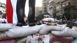 A poster of deposed Egyptian President Mohamed Mursi is seen on a make-shift barrier of sand bags made by members of the Muslim Brotherhood and Musi supporters to protect the sit-in area of Rab'a al- Adawiya Square,