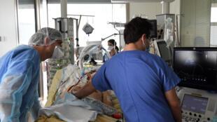 Des membres du personnel de santé soignent un patient atteint du Covid-19 au service de réanimation de l'hôpital Ambroise-Paré, à Boulogne-Billancourt. Plus de 5 950 patients étaient en réanimation mardi13 avril, un chiffre jamais atteint depuis la première vague de la pandémie il y a un an.