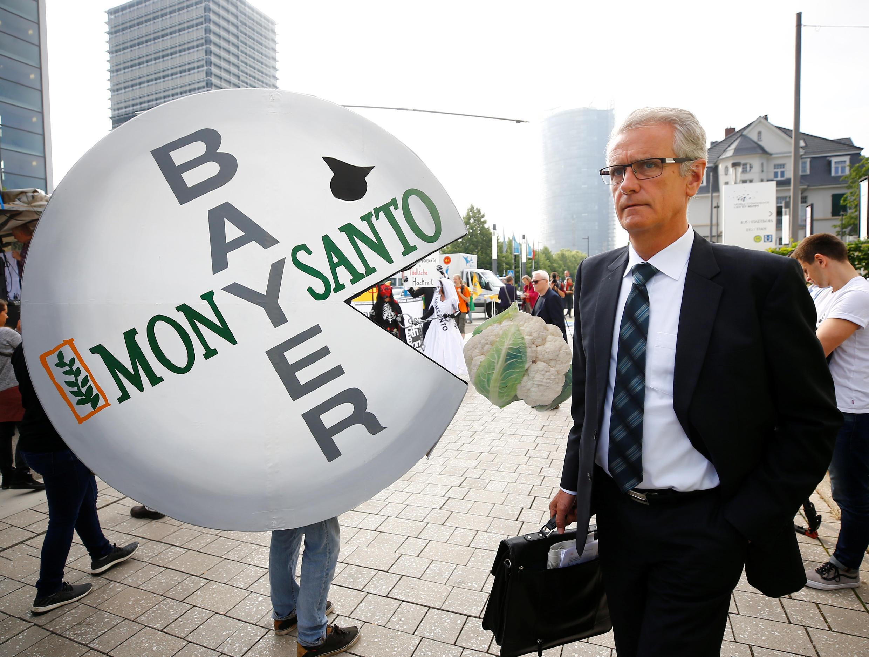 Un actionnaire de Bayer arrive à la réunion annuelle des actionnaires, pendant que des militants manifestent contre le rachat du géant Monsanto par le groupe allemand.