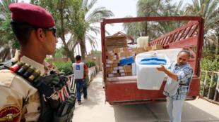 Un membre de la Haute commission électorale indépendante irakienne distribue du matériel électoral à Basra le 6 mai 2018.