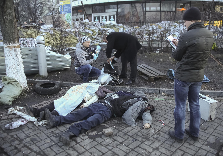 Фотограф агентства «Рейтер» сфотографировал тела двух погибших у станции метро на углу площади Независимости, Киев, 18 февраля 2014.