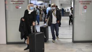 Unos turistas con mascarilla llegan al aeropuerto internacional de Heraklion para pasar una vacaciones en la isla griega de Creta, el 14 de mayo de 2021