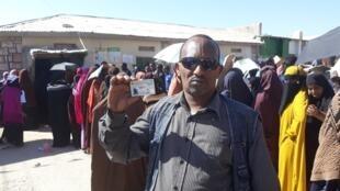 Un électeur brandit sa carte devant une file d'attente devant un bureau de vote du Somaliland, le 13 novembre 2017.