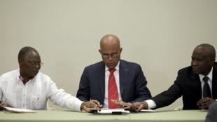 Michel Martelly, entouré du président du Sénat Jocelerme Privert (à gauche) et de Cholcer Chanzy, le président de la Chambre des représentants lors de la signature de l'accord pour l'élection d'un président intérimaire.