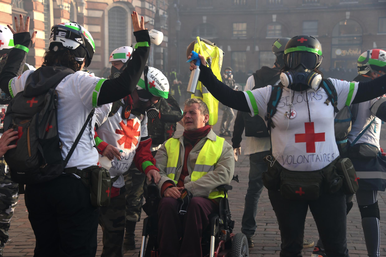 Los médicos benévolos que asisten a las manifestaciones de los Chalecos Amarillos tratan de socorrer a un manifestante rociado de gas lacrimógeno por un policía en Toulouse, el 9 de febrero de 2019.