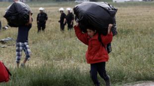 Crianças deixam o campo de refugiados de Idomeni, na Grécia.