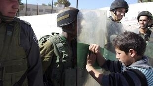 Menino palestino empurra soldado israelense durante manifestação na Cisjordânia.