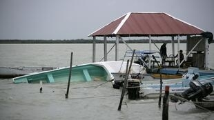 A partially submerged boat floats in the sea in Chetumal, Mexico