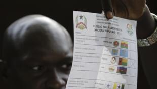 O presidente de uma mesa de assembleia de voto mostra um boletim de voto durante a contagem de votos.