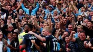 Daruruwan magoya bayan Manchester City, yayin taya 'yan wasan kungiyar da suka hada da Bernardo Silva, raheem Sterling da Kevin De Bryune murnar samun nasarar jefa kwallo a ragar abokan hamayya.
