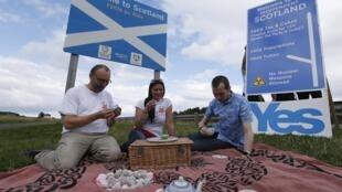 Des partisans pour le «oui» à l'indépendance de l'Ecosse distribuent du thé et des gateaux gratuitement, à la frontière entre l'Angleterre et l'Ecosse, le 7 septembre 2014.