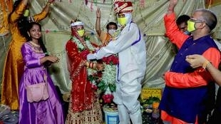 A couple get married in India's western state of Maharashtra wearing PPE kit while guests maintain social distance.