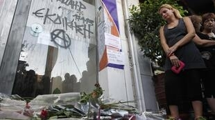 Gregos depositam flores no local onde o rapper Pavlos Fyssas foi assassinado em 18 de setembro de 2013.