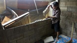 A villager clears his house in Chiang Rai province, north of Bangkok, 25 March 2011
