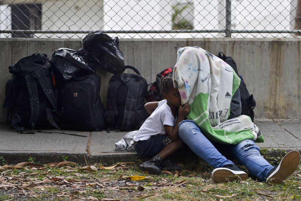 Uma migrante haitiana e seu filho aguardam atendimento no escritório para imigrantes de Cali, na Colômbia, no dia 16 de agosto de 2016.
