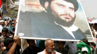 Un poster de Moqtada Sadr brandi dans la foule, à Sadr City, Bagdad.