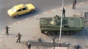 Sur cette photo d'archive, un tank et des soldats algériens patrouillent dans Alger, le 12 octobre 1988, une semaine après le début des émeutes.