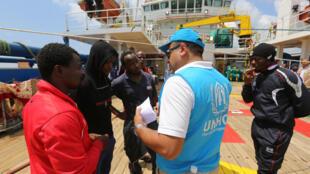 Des migrants africains échangent avec un agent du Haut-Commissariat de l'ONU pour les réfugiés, à bord du navire Sarost 5, dans le port tunisien de Zarzis, le 1er août 2018.