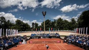 El italiano Lorenzo Musetti (primer plano, delante) sirve contra el griego Stefanos Tsitsipas (al fondo) durante la semifinal del torneo de tenis ATP de Lyon, en el Lyon Open Parc, el 22 de mayo de 2021.
