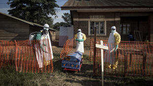 Medical workers disinfect the coffin of an Ebola victim in 2018, during an outbreak in the Democratic Republic of Congo.