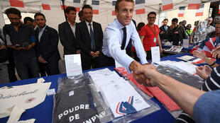 French President Emmanuel Macron shakes hands with visitors next to items for sale as the Elysee Palace opened its doors to the public in Paris, France, September 15, 2018, as part of France's Heritage Days.