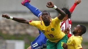 Les Camerounais Mohammadou Idrissou (au centre) et Cedric Loé (à droite) lors d'un match face au Paraguay, le 29 mai 2014.