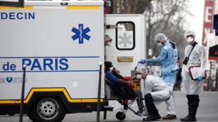 Nhân viên cấp cứu di chuyển bệnh nhân bị nghi nhiểm Covid-19 từ nhà đến bệnh viện tại Paris (Pháp) ngày 20/03/ 2020.