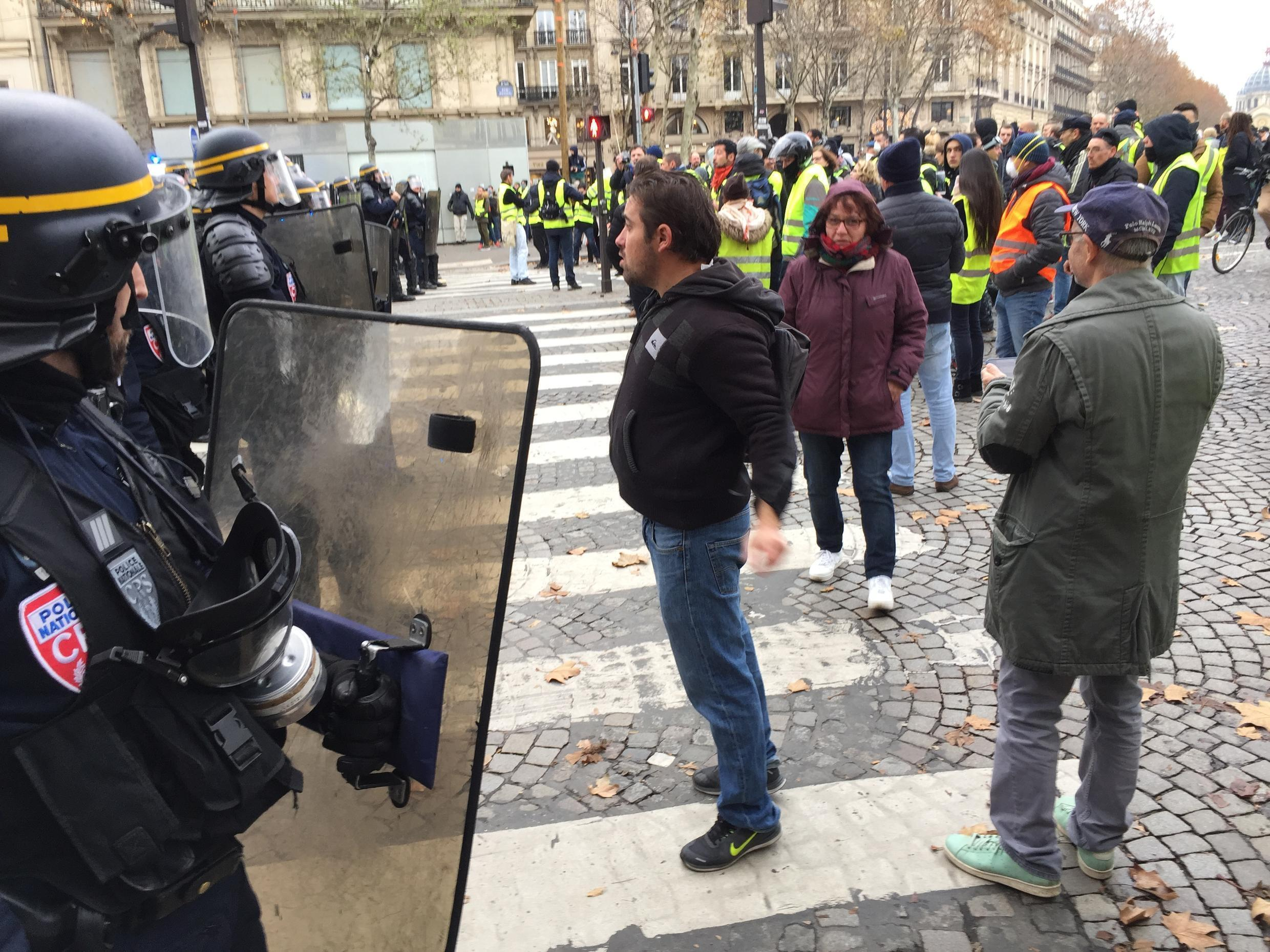 A protester confronts riot police in Paris on Saturday