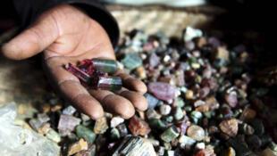A Congolese mineral trader displays semi-precious tourmaline gem stones