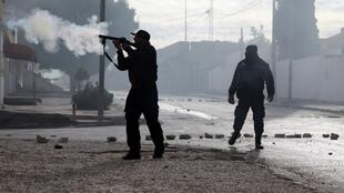 Tunisian policemen fire teargas towards protesters during a demonstration in the central Tunisian city of Kasserine.