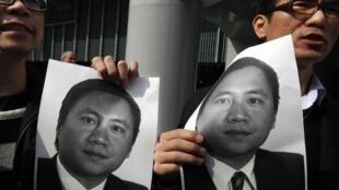 香港民主派人士舉着民運人士王丹的照片向當局抗議。