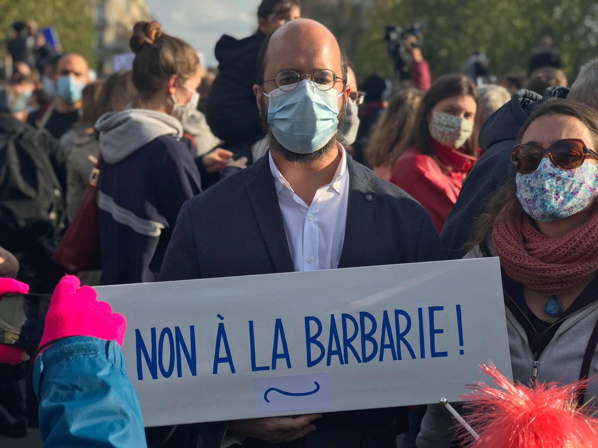 """Акция памяти убитого террористом учителя Самюэля Пати. Плакат """"Нет варварству!"""" Площадь Республики в Париже, 18 октября 2020."""