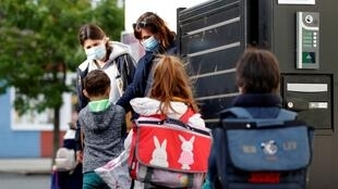 Crianças lavam as mãos à entrada da escola,a 12 de Maio 2020, na reabertura parcial das escolas primárias e infantários em França