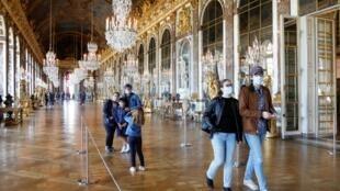 Des visiteurs portant des masques protecteurs dans la Galerie des Glaces du château de Versailles le jour de sa réouverture le 6 juin 2020.