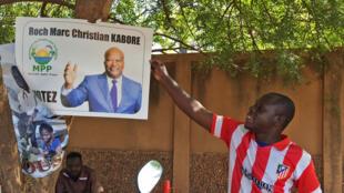 Un homme tient une affiche de Roch Marc Christian Kaboré du Mouvement du peuple pour le progrès (MPP)
