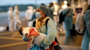 A Vietnamese woman repatriated from Wuhan, where the SARS-like novel coronavirus originated, carries a child as she walks upon her arrival at the Van Don airport in Vietnam's Quang Ninh province on February 10, 2020.