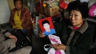 Une mère montre une photo de son fils disparu le 7 novembre 2009
