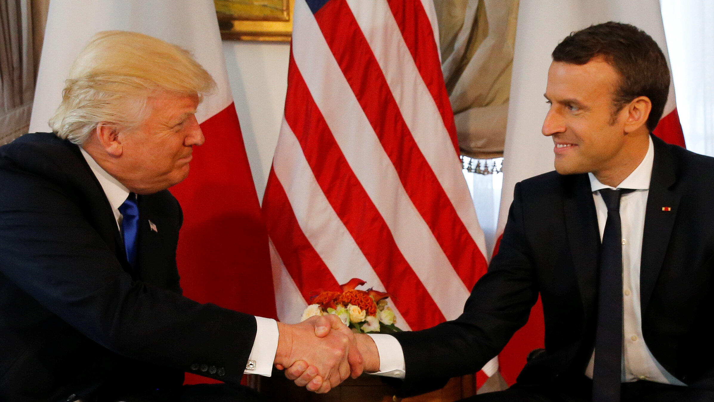US President Donald Trump shakes jhands with Emmanuel Macron for a long time at a Nato summit in May